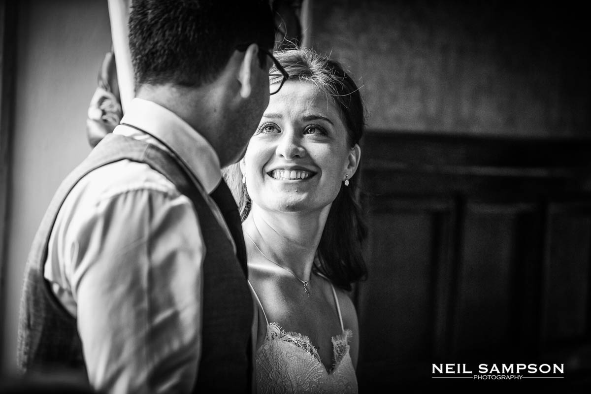 A bride smiles broadly at the groom