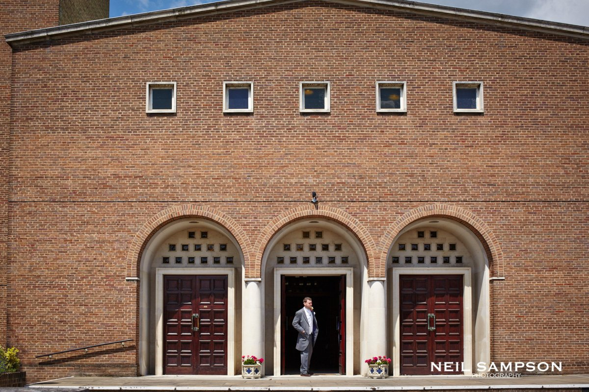 a groom looks out the front of the church waiting for the bride