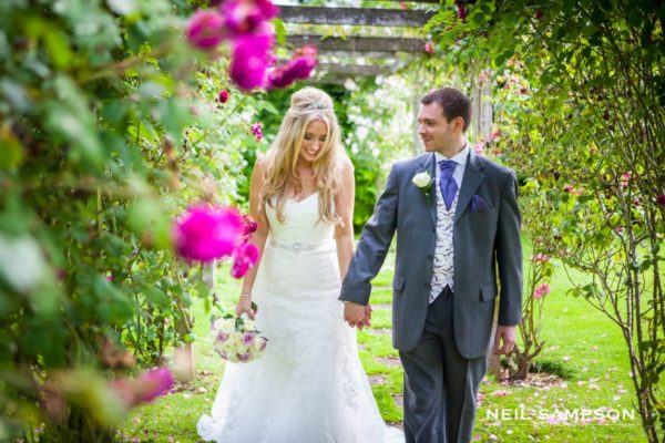 A newly married bride and groom walk through the rose garden at Micklefield hall