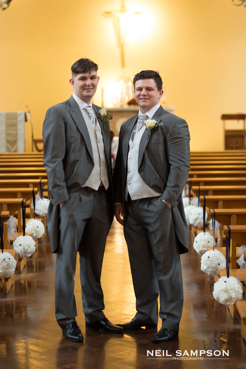 The groom and best man pose for a photo at St Theresa's church in Harrow