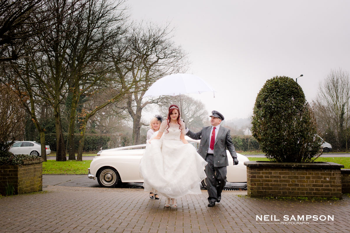 The chauffeur holds the umbrella for the bride as she arrives in the snow at church