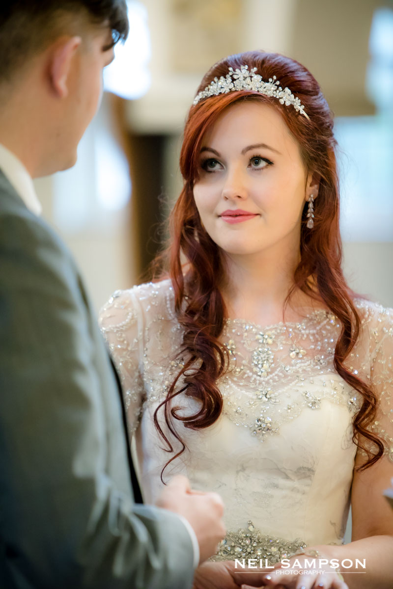 The bride looks lovingly at the groom as they exchange rings