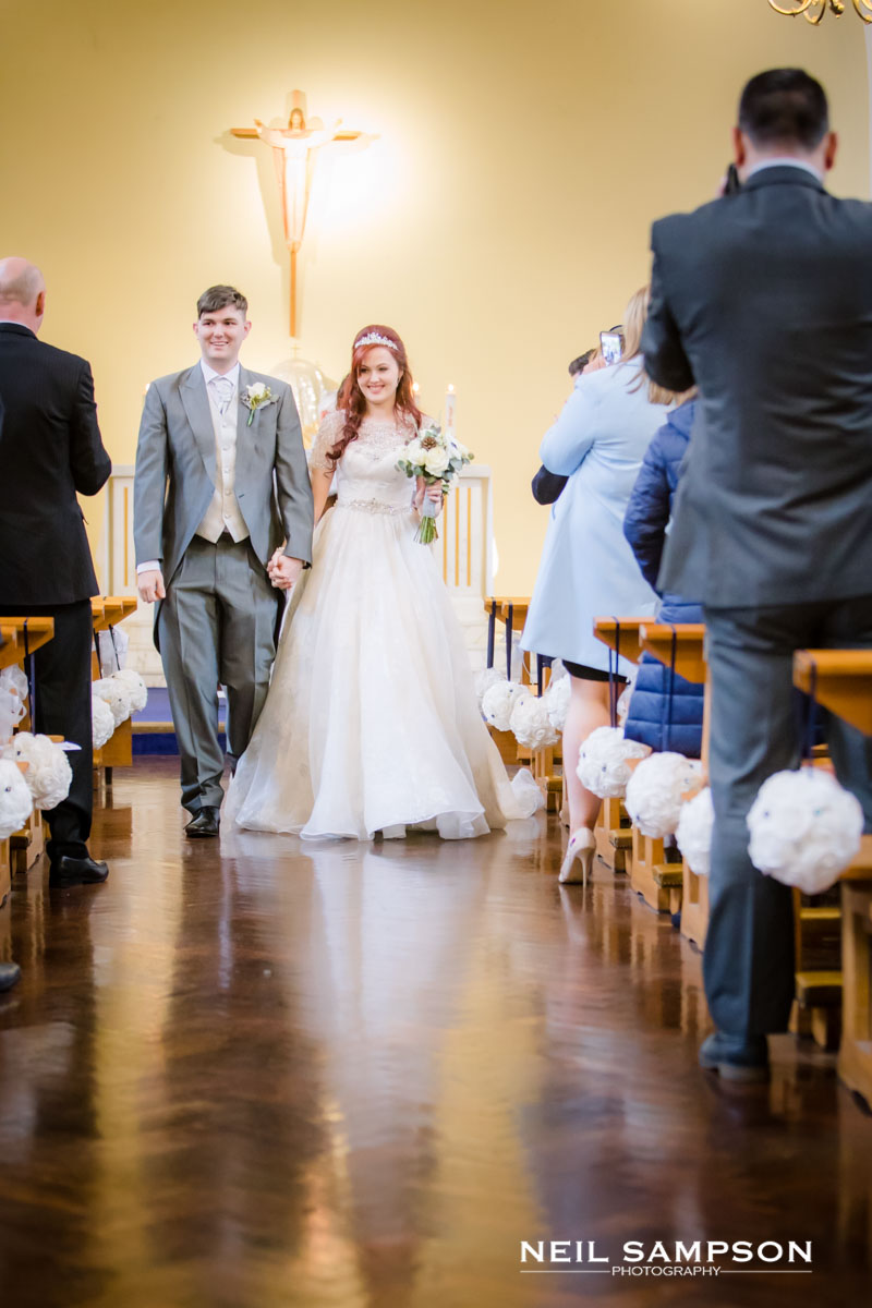 The bride and groom walk down the aisle at St Theresa's church in harrow