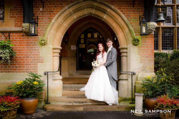 The bride and groom stand on the front steps of Grim's Dyke hotel in Harrow