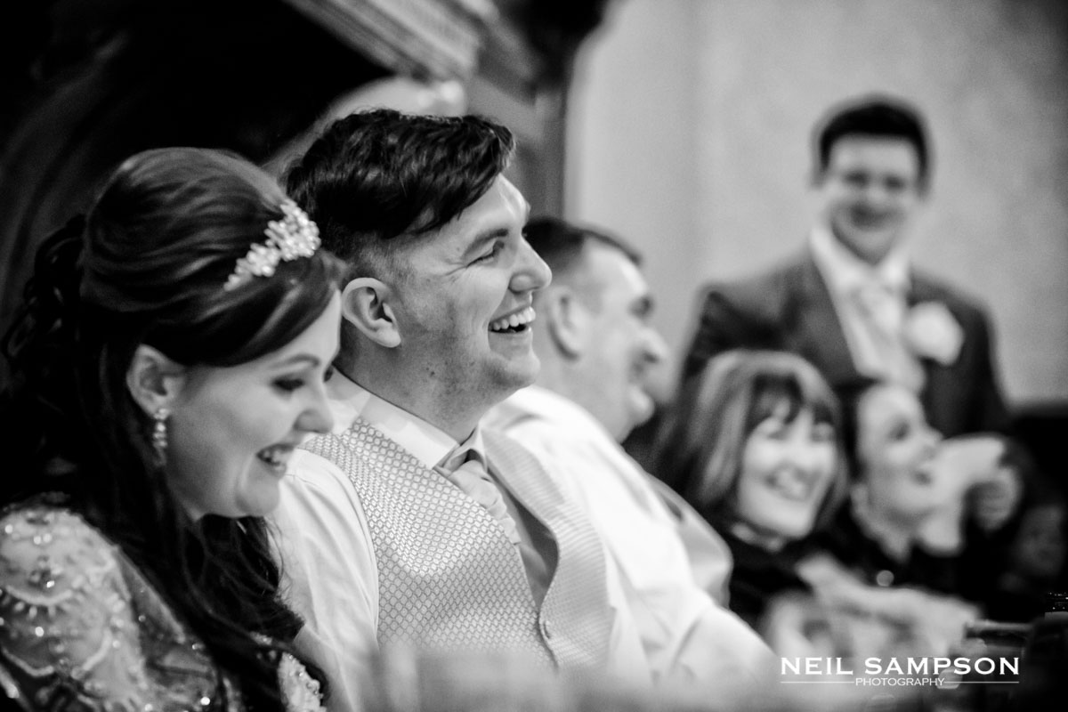 The groom laughs during the best man speech at Grim's Dyke hotel