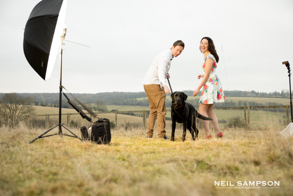 A set up shot showing a large octabox flash and a bare flash lighting a couple posing with their dog for an engagement photo