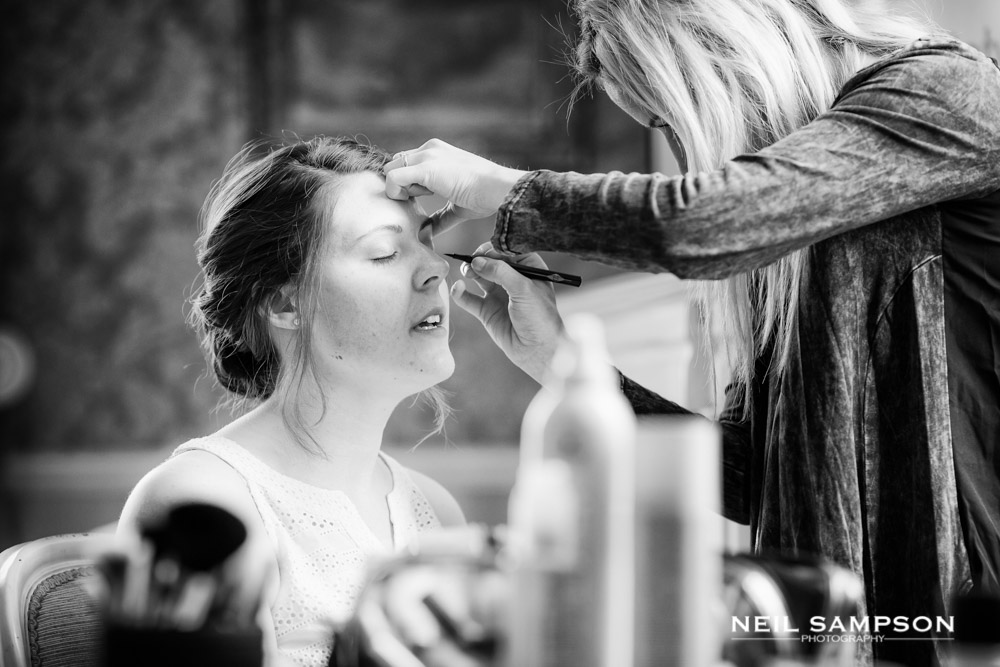The bride has her make up applied before her wedding