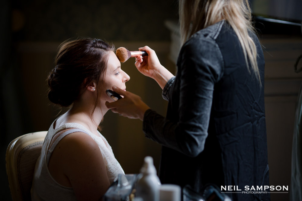 The bride has her makeup done in side window light