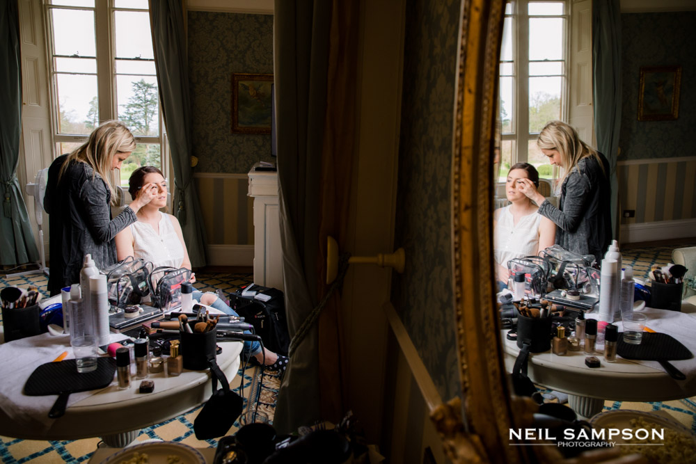 The bride is reflected in a mirror as she gets ready for her wedding
