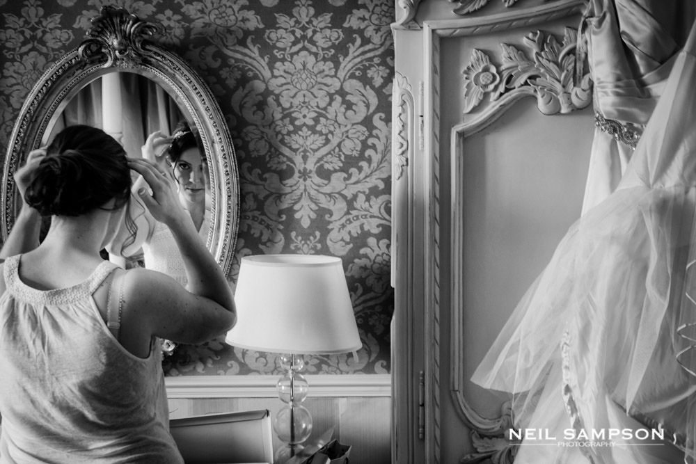 The bride looks at herself in the mirror and makes final adjustments