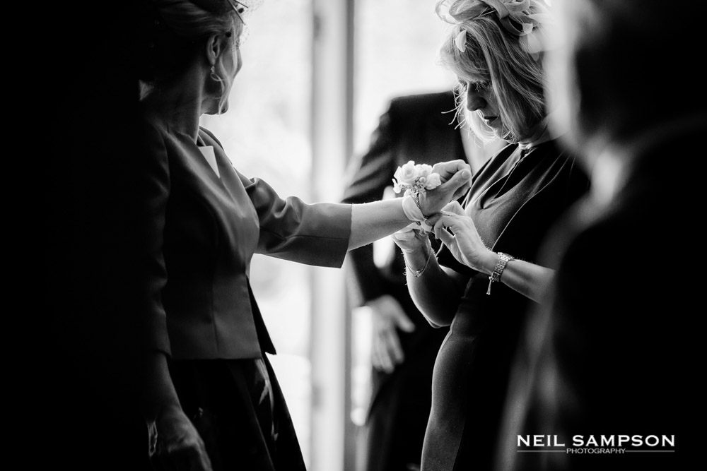 Helping the groom's mother put a flower on her wrist