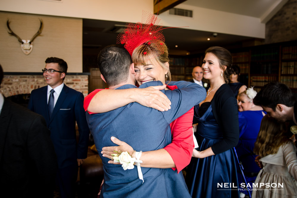 Guests hug each other before the wedding