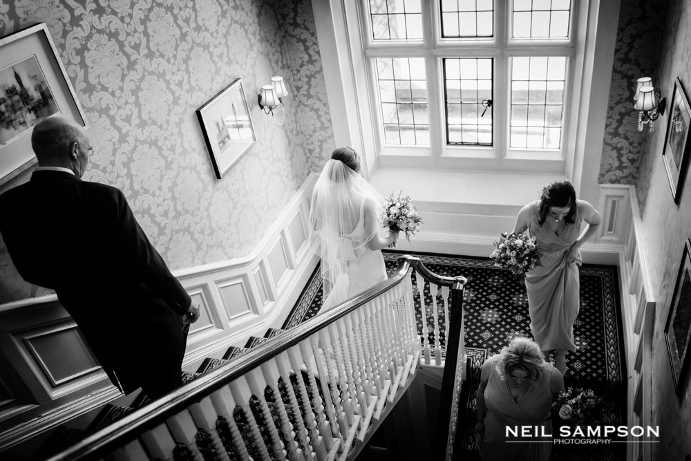 The bride, her father and the bridesmaids head down the stairs at Shendish Manor