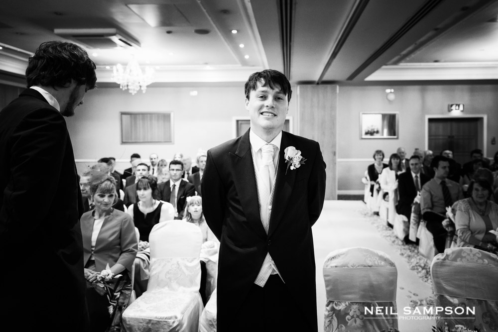 The groom smiles while waiting for his bride to arrive at the wedding ceremony