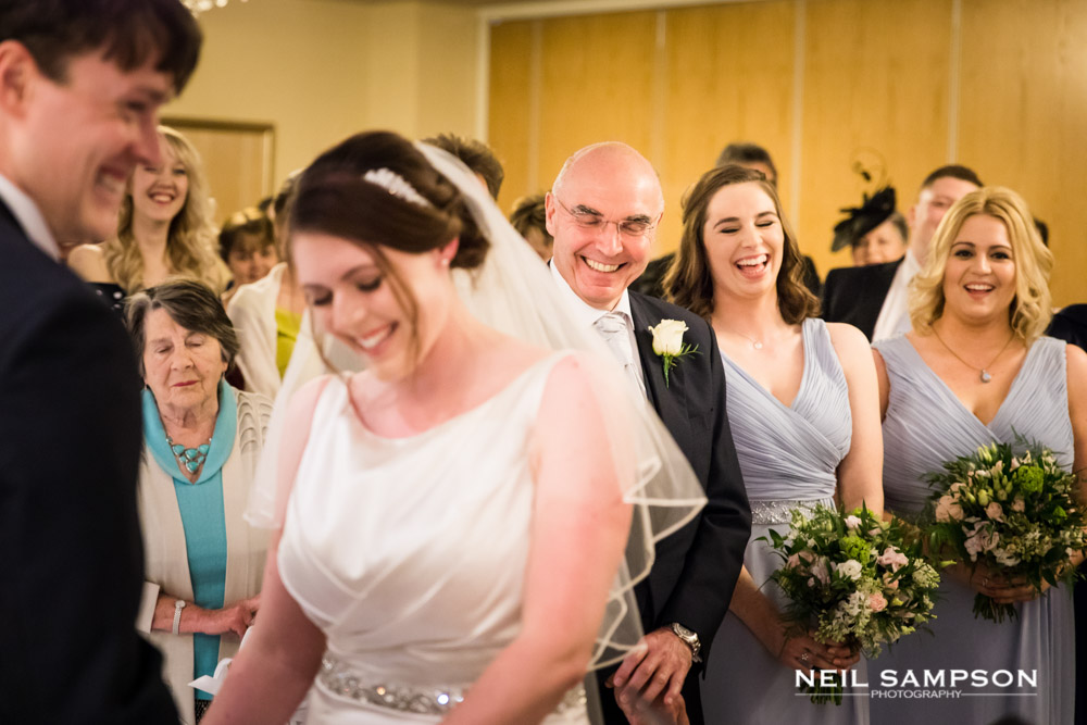 Smiles all round during the wedding ceremony as the bridesmaids laugh in the background