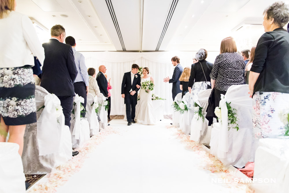 The bride and groom walk down the aisle on a white carpet at shendish manor hotel