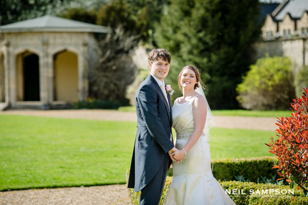 A traditional pose of the bride and groom with the gardens at shendish manor in the background