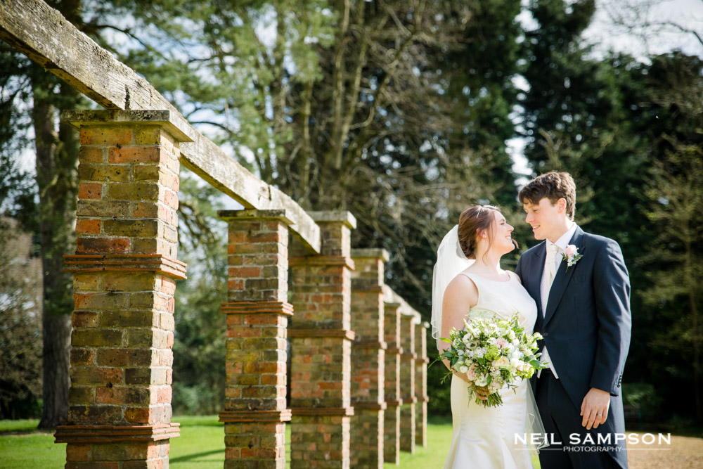 The bride and groom look at each other near a brick feature at shendish in Apsley