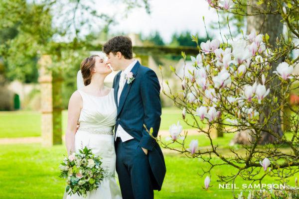The bride and groom kiss near a magnolia tree