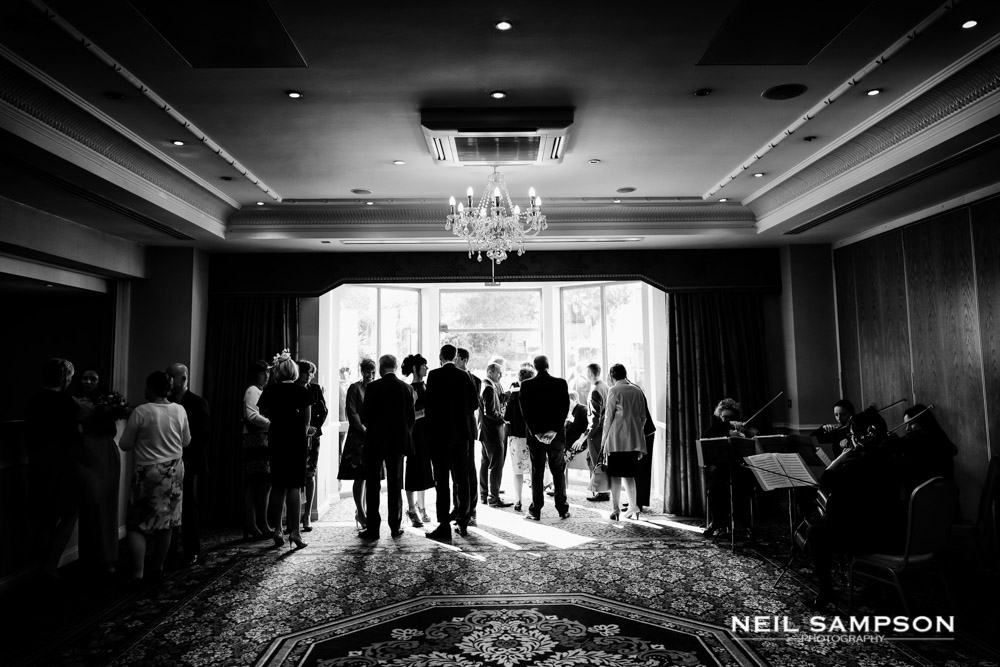 A backlit shot indoors as guests gather at the drinks reception