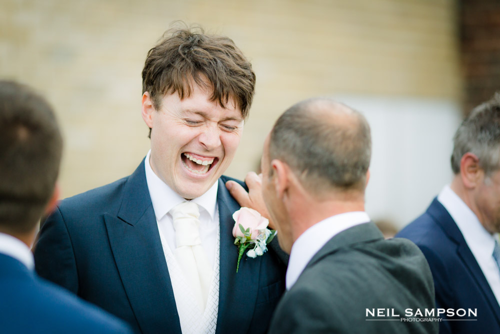 The groom laughs loudly while talking to a guest at his wedding