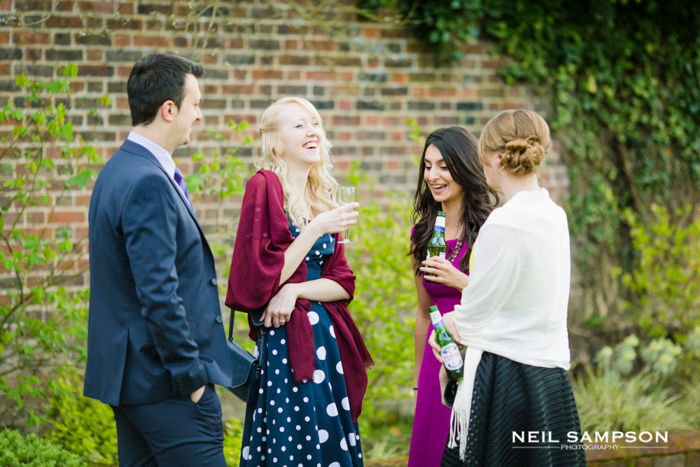 Guests enjoy a joke in the gardens during a wedding