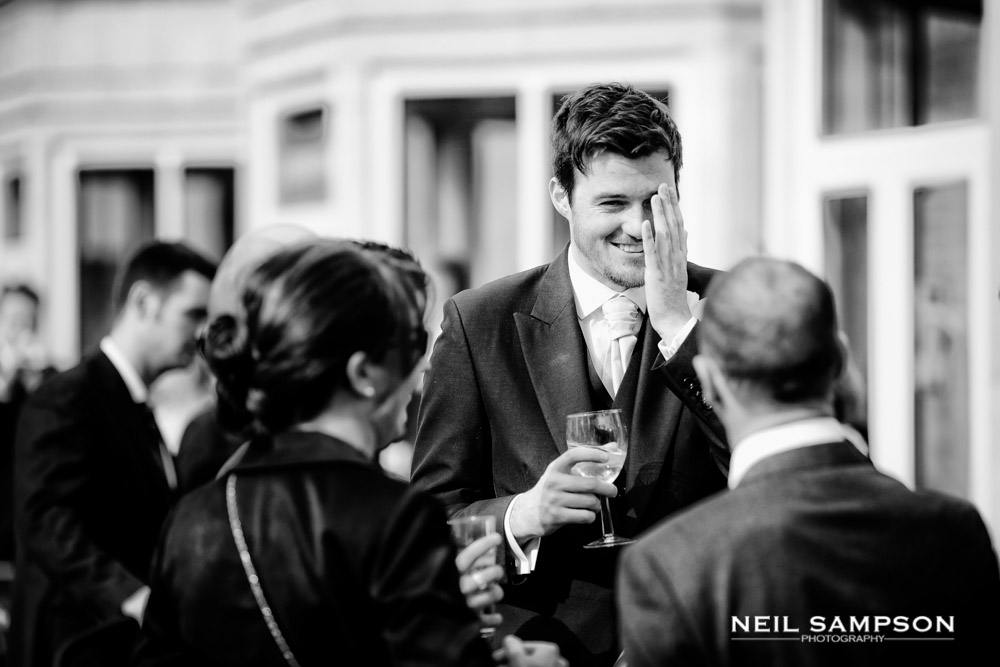 A guest smiles ruefully during the wedding drinks reception