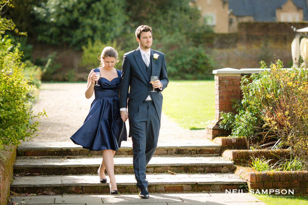 Two guests walk holding hands in the gardens at Shendish Manor