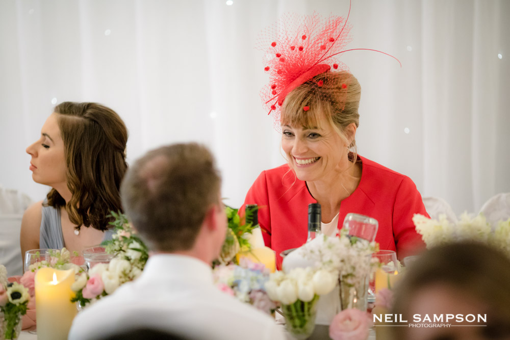 A lady in a red dress and fascinator at a wedding in hemel hempstead