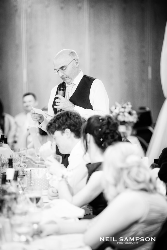 The bride's father looking thoughtfully at his notes during his speech