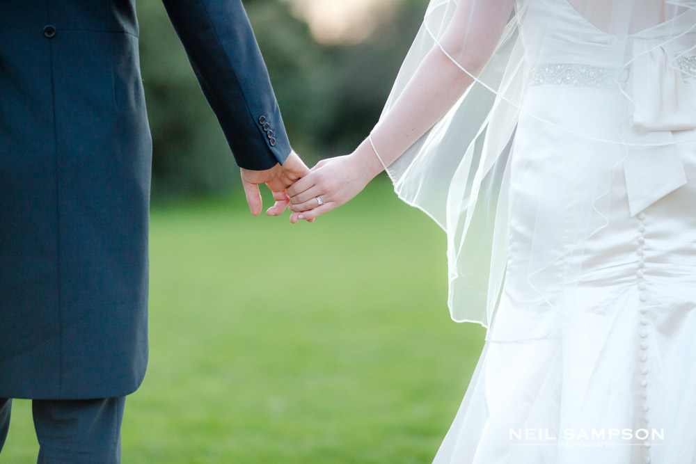 The bride and groom loosely hold hands