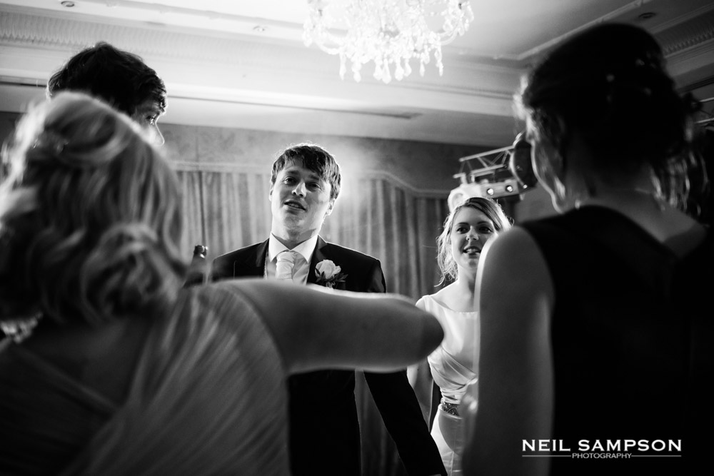 A black and white photo of the groom on the dance floor surrounded by guests