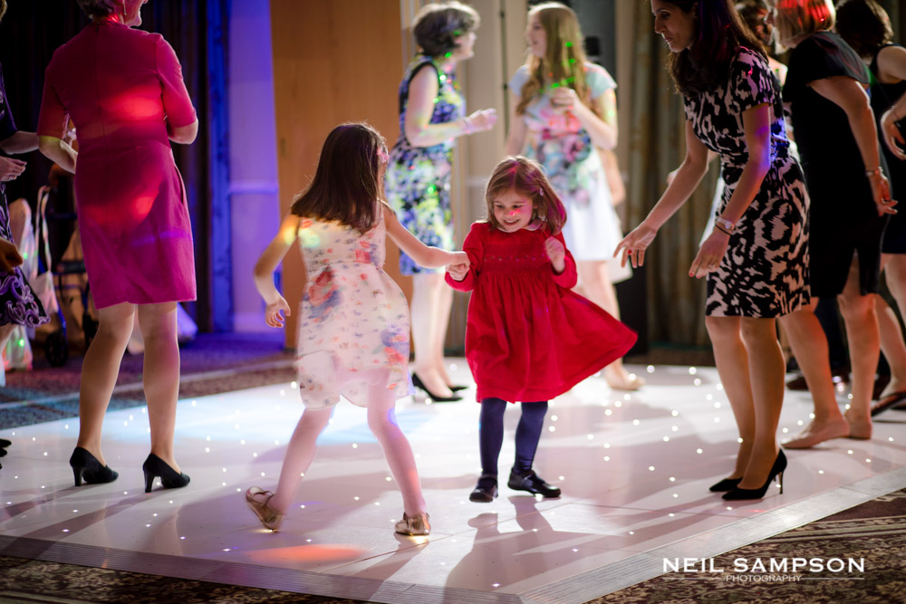 Two young children, one in a red dress, dance on the dance floor
