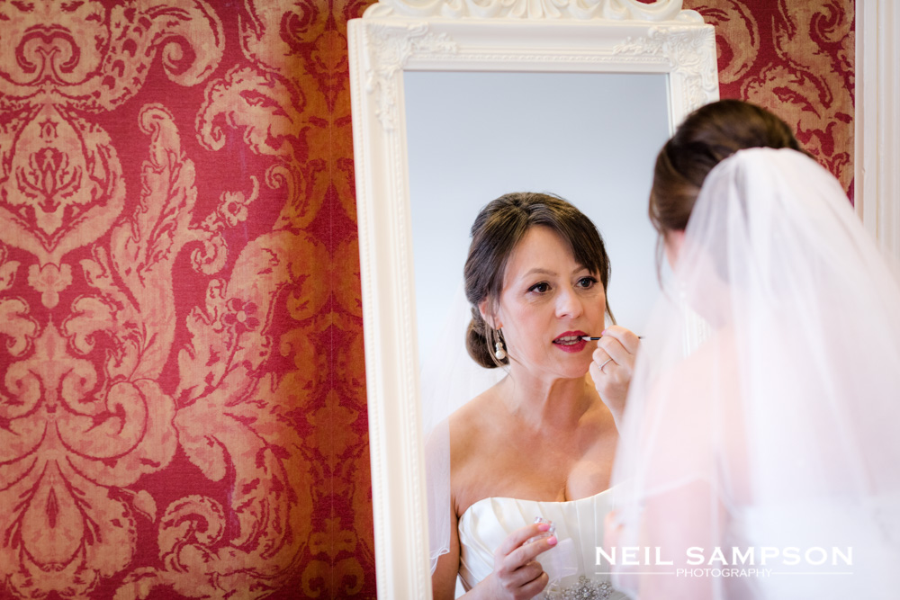 A bride puts on make up while looking in the mirror