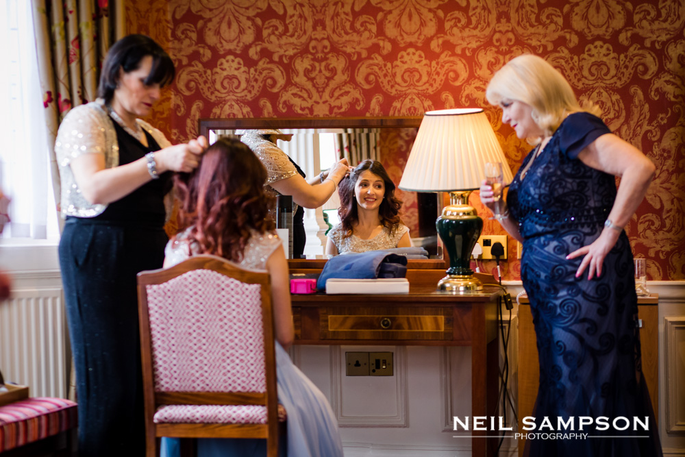 A bridesmaid has her hair done at grims dyke hotel