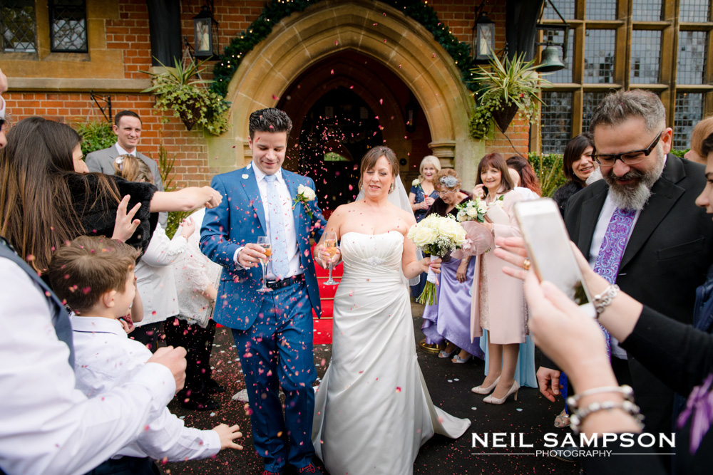 The guests throw confetti at the bride and groom