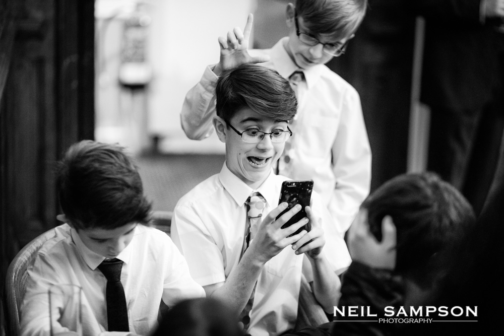 Children play on phones during the wedding reception