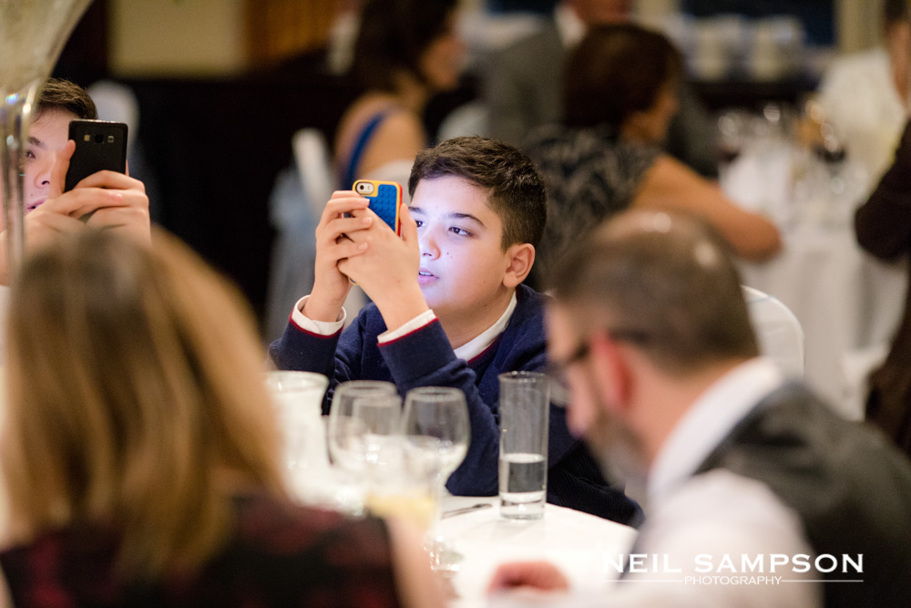 Kids on phones at a wedding