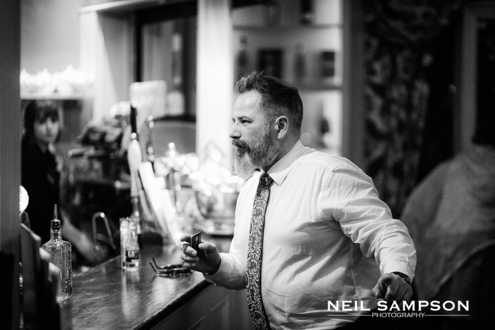 A guest orders a drink at the bar in grims dyke hotel