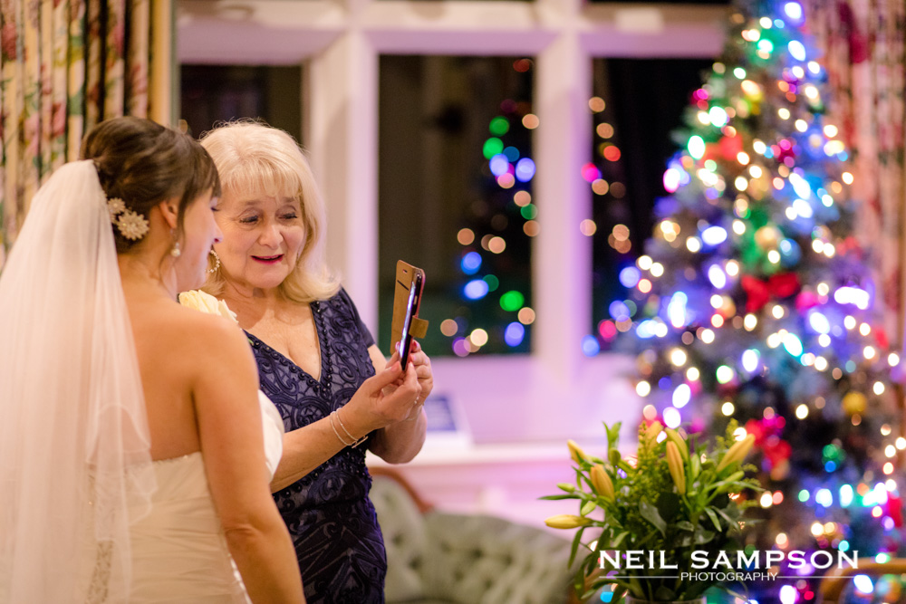 The bride looks at a photograph on a phone with a christmas tree in the background