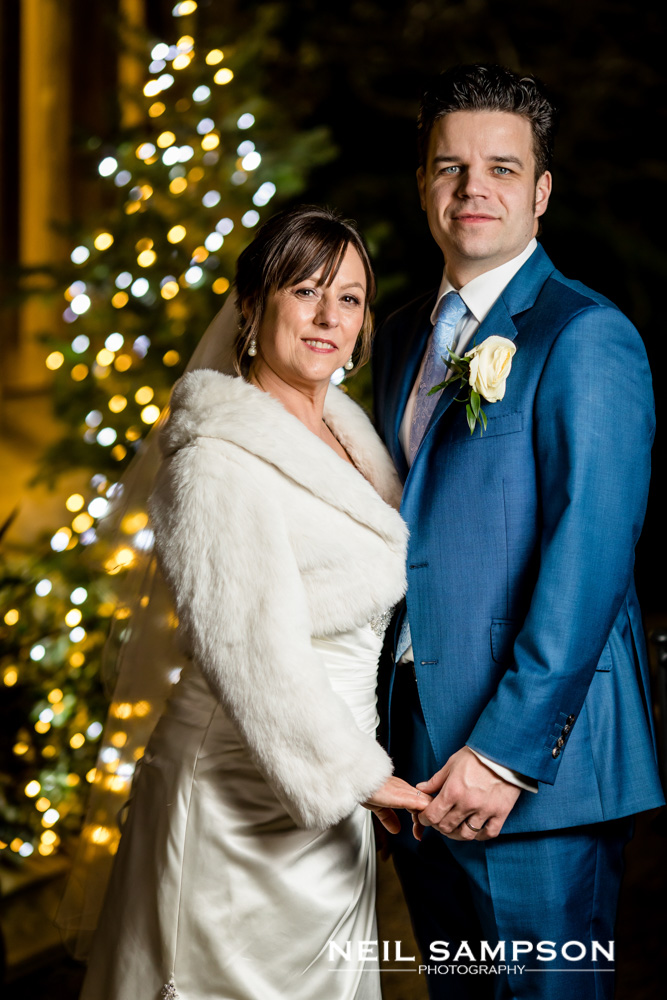 The bride and groom hold hands in front of a christmas tree at grims dyke