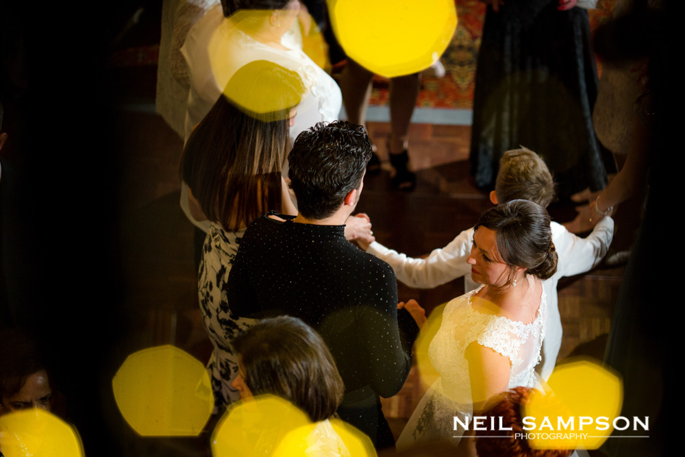 The bride and groom on a busy dance floor
