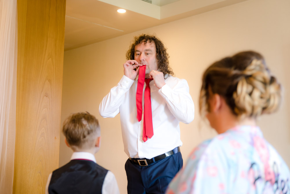 a man pretends his tie is a musical instrument