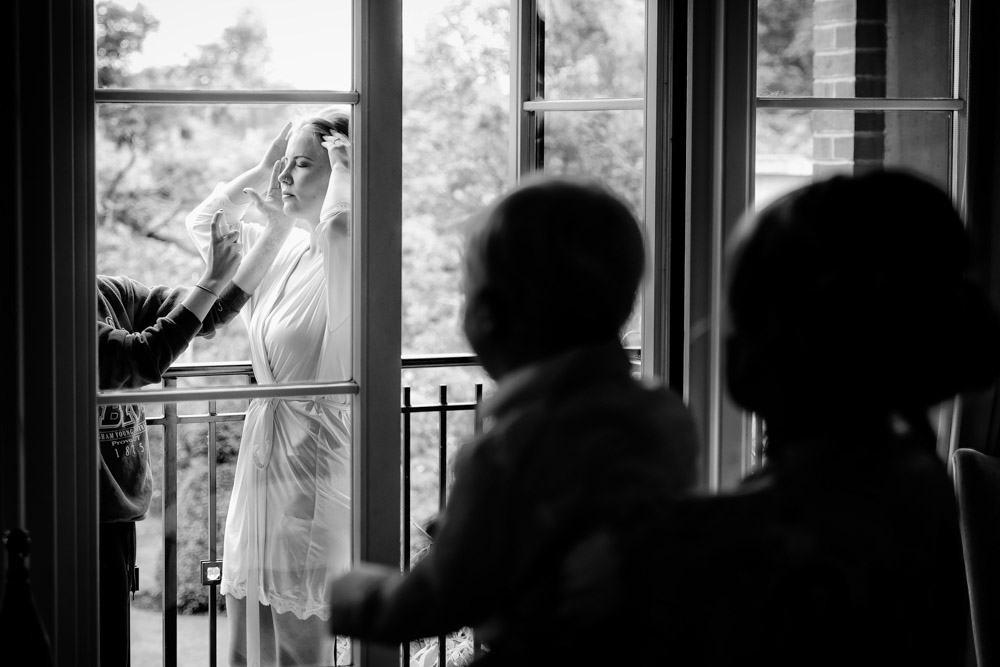 A bride has her make up done on a balcony