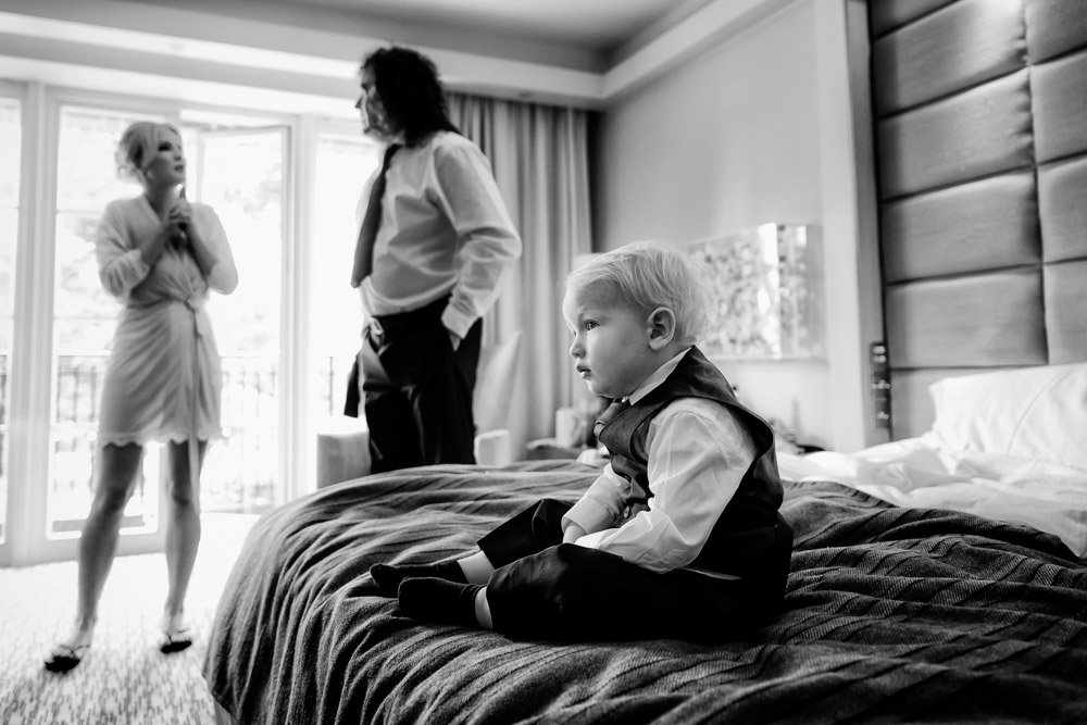 A small boy on a bed while the bride talks to her father