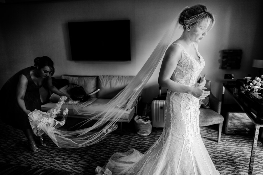 The bride has her veil arranged by a bridesmaid