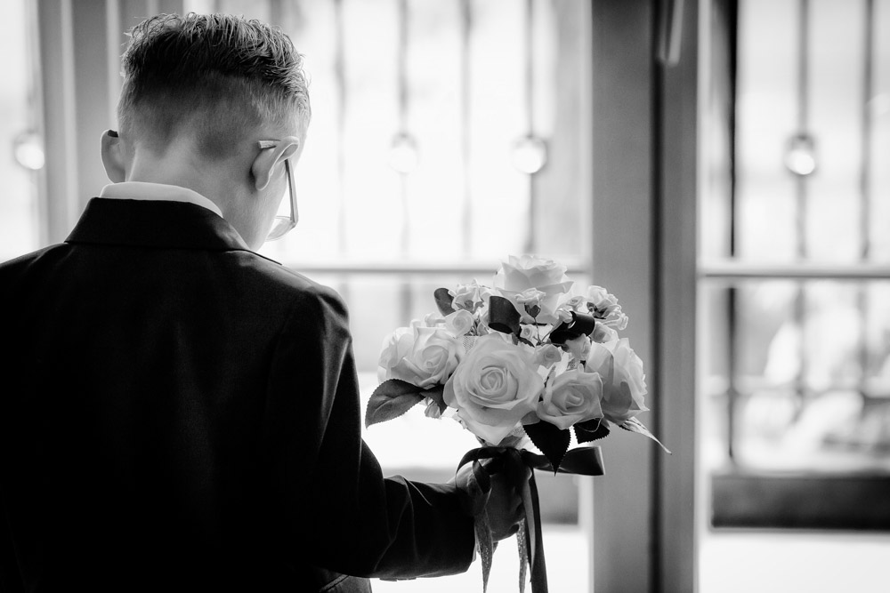 A young page boy holds the bride's bouquet