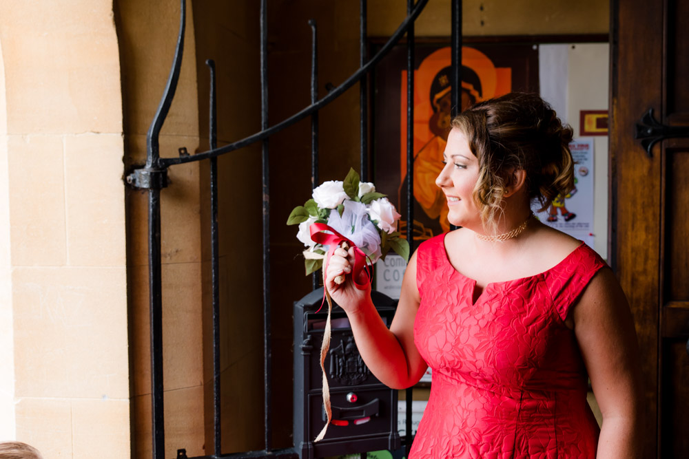 A bridesmaid smiles as she waits for the bride at a watford church wedding