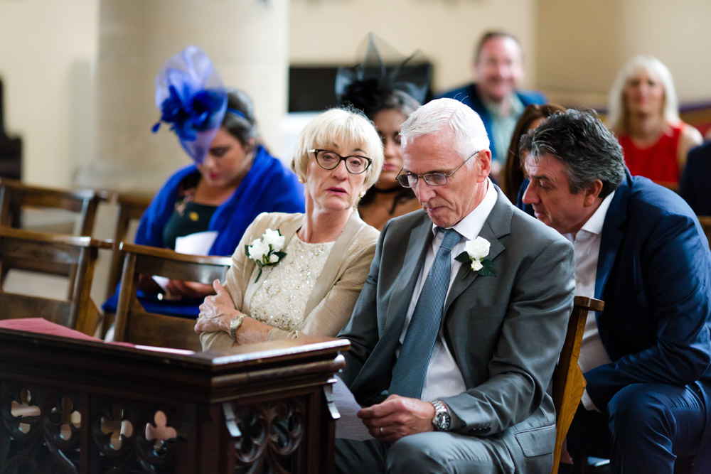 The groom's parents wait in church