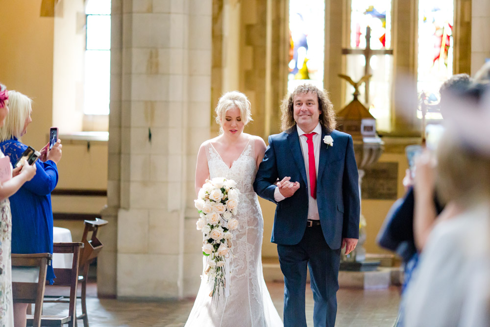 The bride walks up the aisle with her father in a watford church
